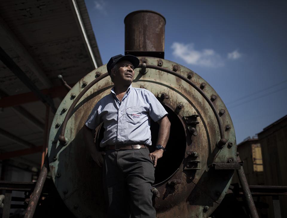 """Alan Roberto Tally Marroquín, """"El Negro"""", de 62 años, fue maquinista durante 38 años. Tally frente a la locomotora alemana 165, de la empresa CRUP, una de las 13 que llegaron a Guatemala después de la Segunda Guerra mundial. [Simone Dalmasso]"""