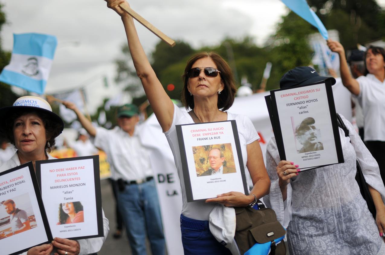 Familiares de ex militares durante la marcha, con retratos de supuestos responsables..