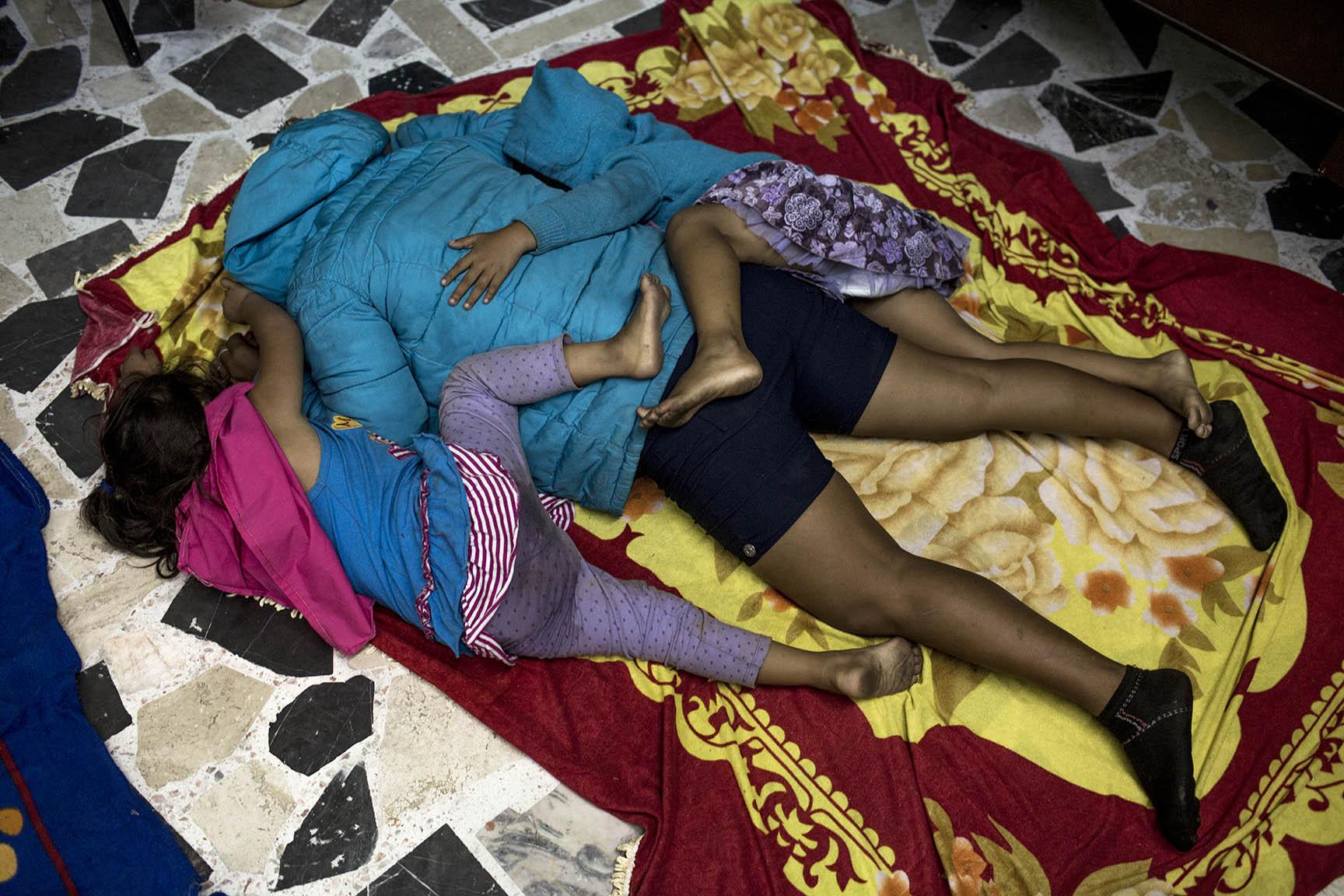 Karen y Seidy Díaz duermen tiradas encima de su mamá, Silvia, al suelo, recién llegadas al albergue de Puebla / Simone Dalmasso