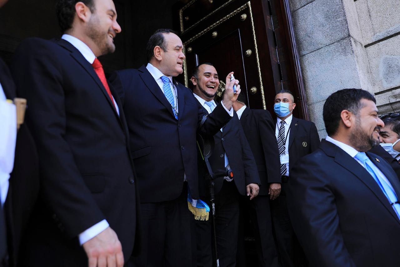 Alejandro Giammattei bromea con unos diputados enseñando spray antibacterial a la prensa mientras sale del Congreso, después de la sesión, el 19 de marzo.