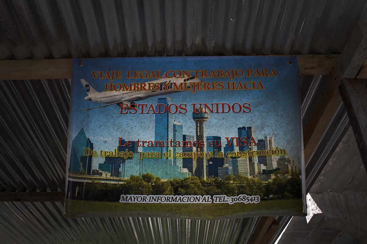 Un cartel que promovía viajes legales a Estados Unidos oxidado bajo el techo de un garaje.