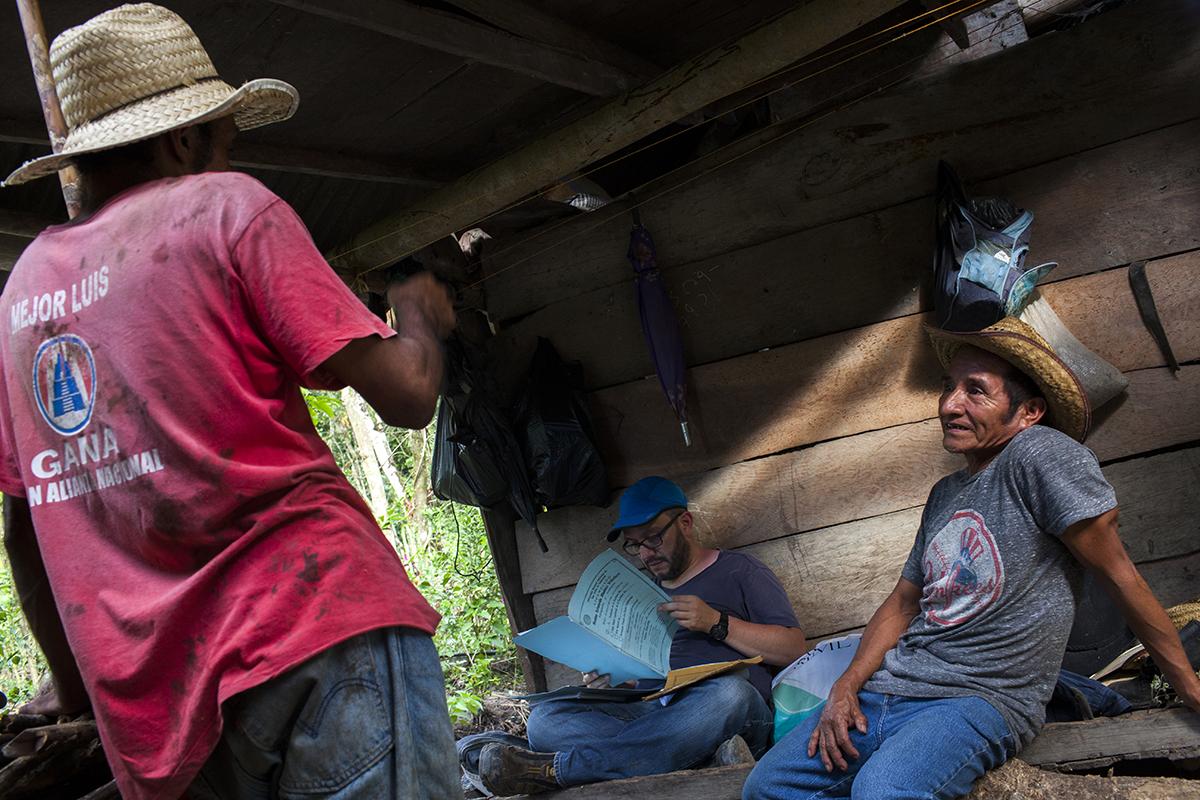 Nicolás Juan Juárez, a la derecha, abuelo de Roberto Ramírez, platica con el alcalde auxiliar, mientras el abogado Solares, chequea el estatus del título de tierra traspasado al coyote.